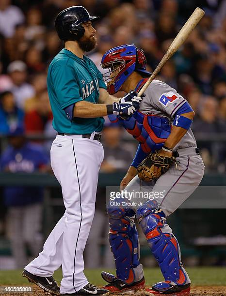 Dustin Ackley of the Seattle Mariners is tagged out by catcher Robinson Chirinos of the Texas Rangers on a strikeout to end the seventh inning with...