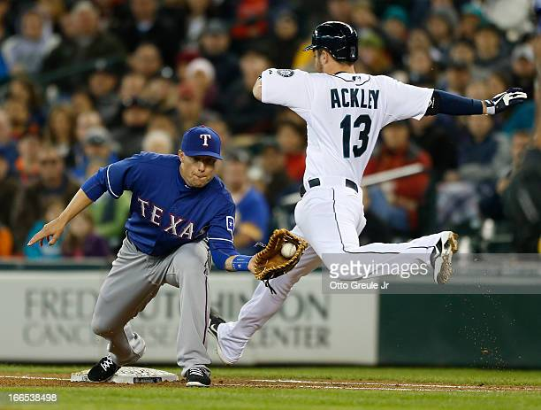 Dustin Ackley of the Seattle Mariners is thrown out at first base on a groundout with two runners on base as Jeff Baker of the Texas Rangers takes...