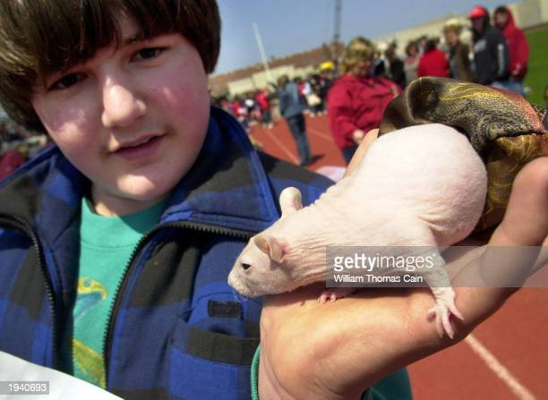 Dustin Baker of Lancaster Pennsylvania holds his Mexican Hairless Rat named Chiquita as they attend the Woofin' Paws Easter Pet Parade and Fashion...