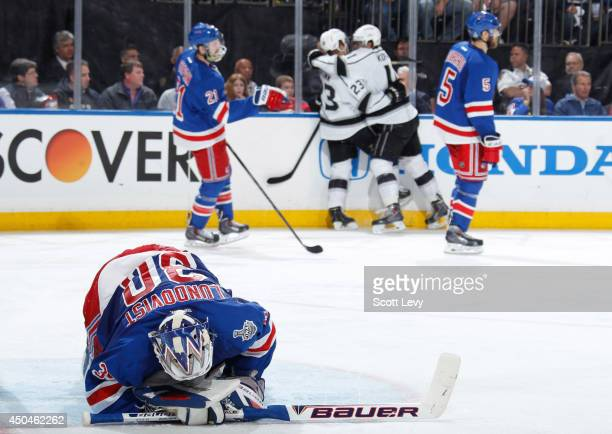 Dustin Brown and Anze Kopitar of the Los Angeles Kings celebrate after a second period goal as Henrik Lundqvist of the New York Rangers lays on the...