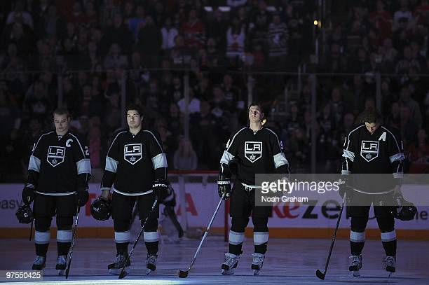 Dustin Brown, Drew Doughty, Ryan Smyth and Anze Kopitar of the Los Angeles Kings stand on the ice during the singing of the National Anthem prior to...