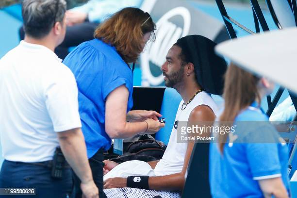Dustin Brown of Germany receives medical attention in his match against Dennis Novak of Austria during day two of 2020 Australian Open Qualifying at...