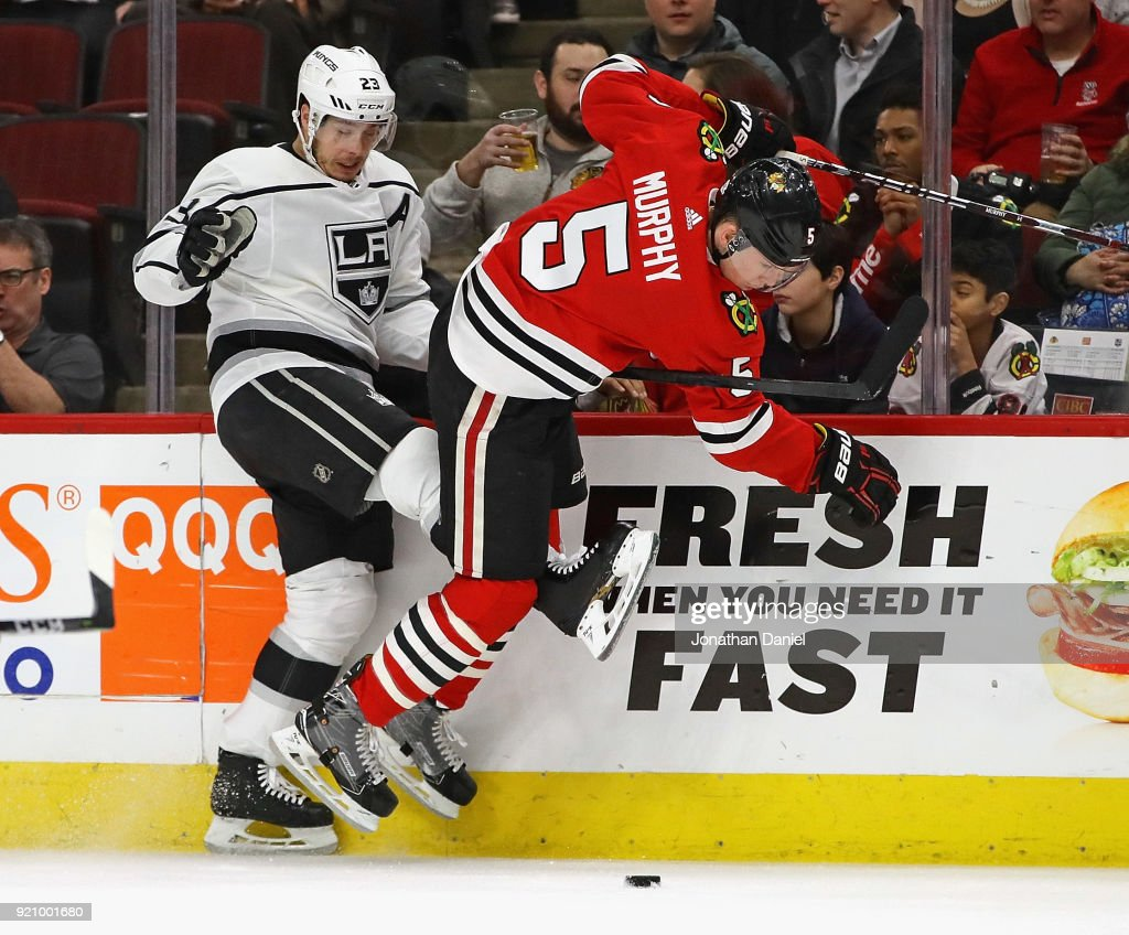 Dustin Brown #23 of the Los Angeles Kings and Connor Murphy #5 of the Chicago Blackhawks battle for the puck along the boards at the United Center on February 19, 2018 in Chicago, Illinois.