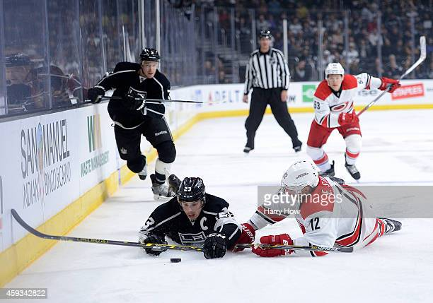 Dustin Brown of the Los Angeles Kings and Eric Staal of the Carolina Hurricanes fall near the puck as Brayden McNabb of the Los Angeles Kings and...