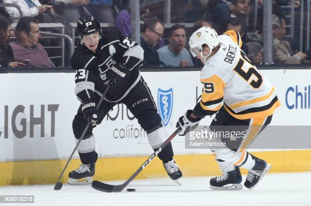 Dustin Brown of the Los Angeles Kings battles for the puck against Jake Guentzel of the Pittsburgh Penguins at STAPLES Center on January 18 2018 in...