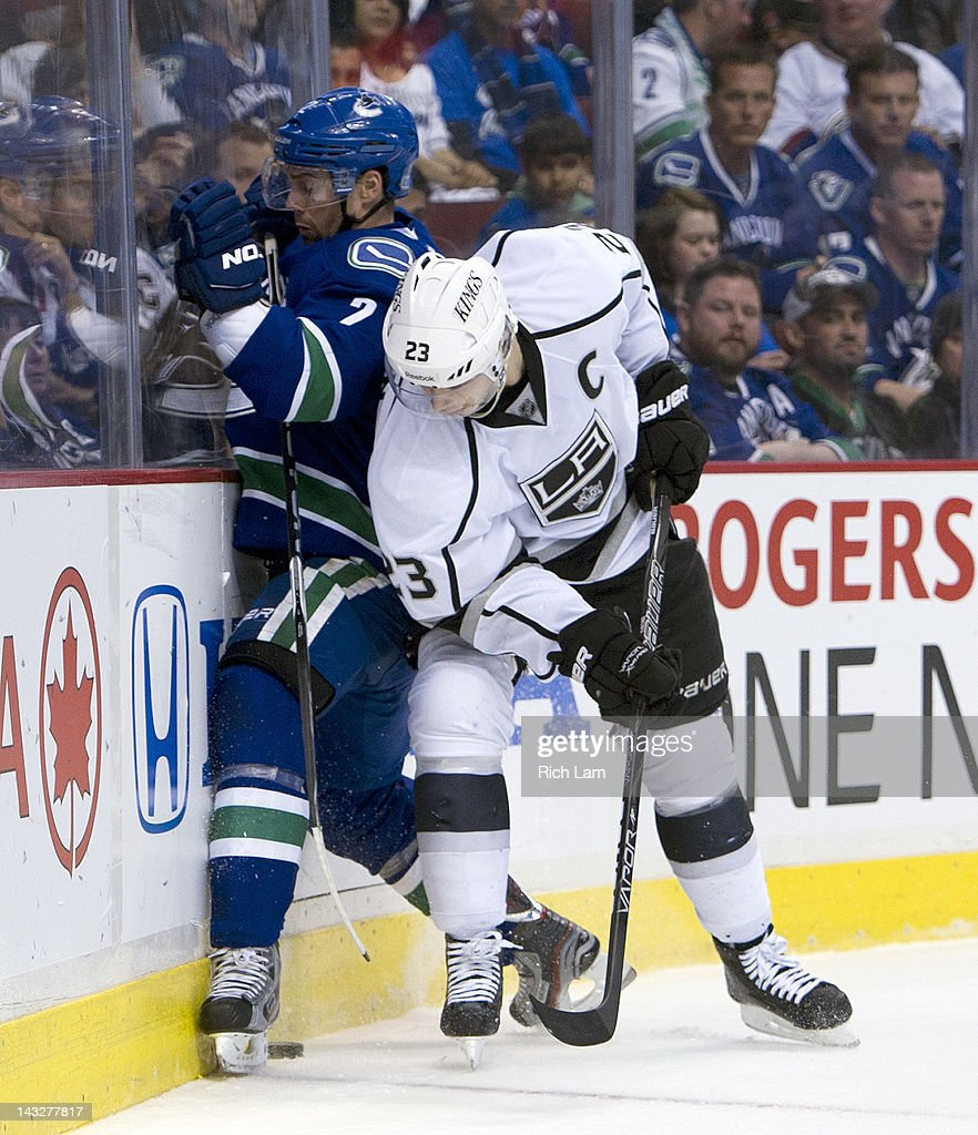 Dustin Brown #23 of the Los Angeles Kings battles with Dan Hamhuis #2 of the Vancouver Canucks for the loose puck during the second period in Game Five of the Western Conference Quarterfinals during the 2012 NHL Stanley Cup Playoffs at Rogers Arena on April 22, 2012 in Vancouver, British Columbia, Canada.