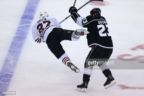 Dustin Brown of the Los Angeles Kings checks Johnny Oduya of the Chicago Blackhawks in the neutral zone in the first period of Game Three of the...