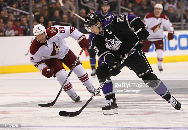 Dustin Brown of the Los Angeles Kings controls the puck near the blueline on his way to a breakaway as Derek Morris of the Phoenix Coyotes gives...