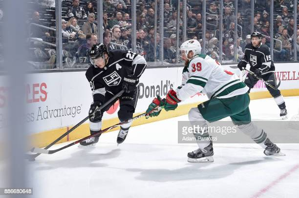 Dustin Brown of the Los Angeles Kings handles the puck against Nate Prosser of the Minnesota Wild at STAPLES Center on December 5 2017 in Los Angeles...