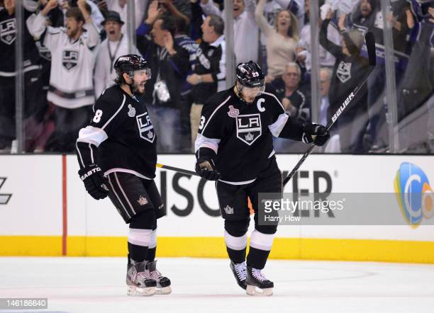 Dustin Brown of the Los Angeles Kings reacts after assisting in a first period goal scored by Jeff Carter against the New Jersey Devils as Drew...