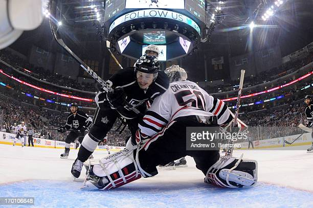Dustin Brown of the Los Angeles Kings runs into Corey Crawford of the Chicago Blackhawks in Game Three of the Western Conference Final during the...
