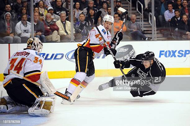 Dustin Brown of the Los Angeles Kings shoots the puck against Mikka Kiprusoff and Chris Butler of the Calgary Flames at Staples Center on January 19...