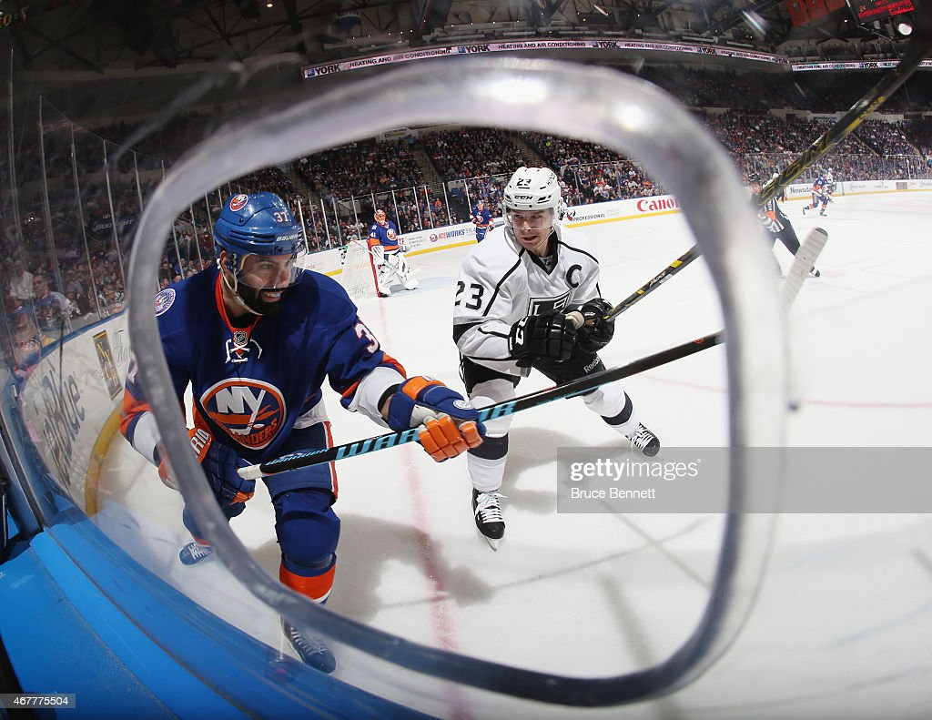 Dustin Brown #23 of the Los Angeles Kings skates in on Brian Strait #37 of the New York Islanders at the Nassau Veterans Memorial Coliseum on March 26, 2015 in Uniondale, New York. The Kings defeated the Islanders 3-2.