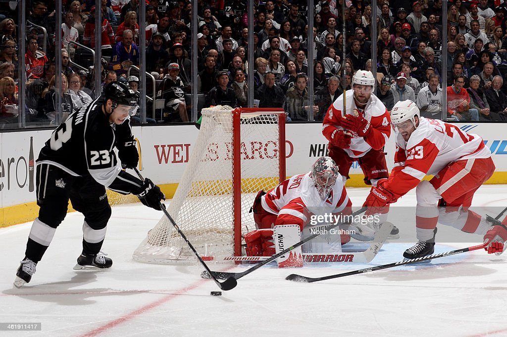 Dustin Brown #23 of the Los Angeles Kings skates with the puck against Jimmy Howard #35 and Brian Lashoff #23 of the Detroit Red Wings at Staples Center on January 11, 2014 in Los Angeles, California.