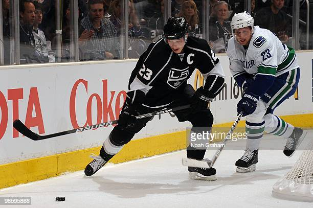 Dustin Brown of the Los Angeles Kings skates with the puck against Alexander Edler of the Vancouver Canucks in Game Three of the Western Conference...