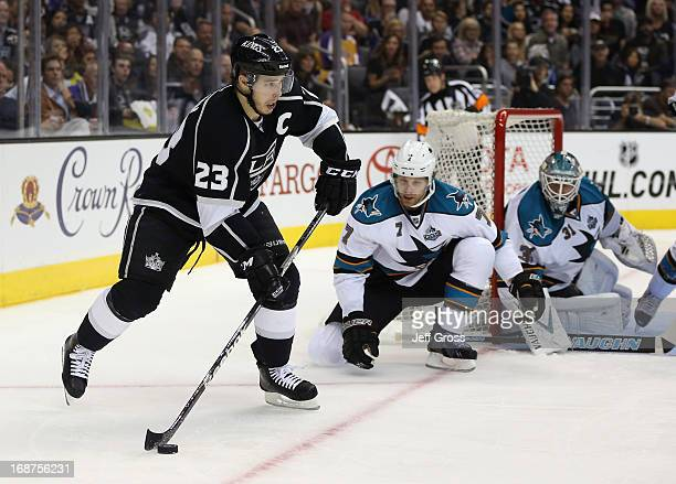 Dustin Brown of the Los Angeles Kings skates with the puck as Brad Stuart and goaltender Antti Niemi of the San Jose Sharks defend in the third...