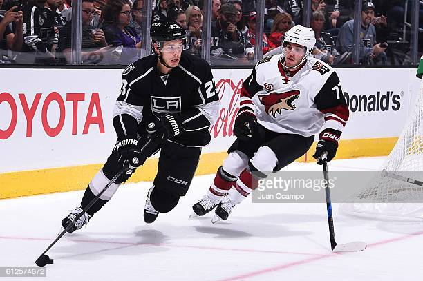 Dustin Brown of the Los Angeles Kings skates with the puck with pressure from Anthony Deangelo of the Arizona Coyotes during a preseason game on...