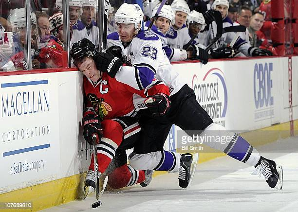 Dustin Brown of the Los Angeles Kings slams Jonathan Toews of the Chicago Blackhawks into the boards on December 19 2010 at the United Center in...
