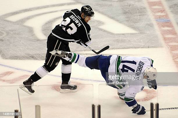 Dustin Brown of the Los Angeles Kings throws the check against Alexandre Burrows of the Vancouver Canucks in Game Four of the Western Conference...