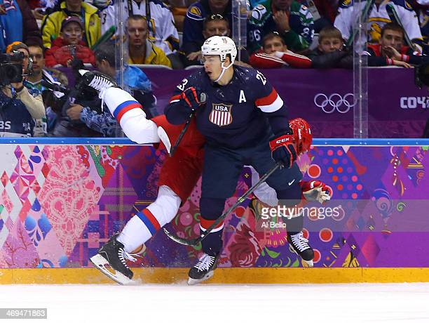 Dustin Brown of United States checks Anton Belov of Russia during the Men's Ice Hockey Preliminary Round Group A game on day eight of the Sochi 2014...