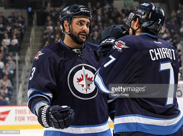 Dustin Byfuglien and Ben Chiarot of the Winnipeg Jets discuss strategy during a third period stoppage in play against the Columbus Blue Jackets at...
