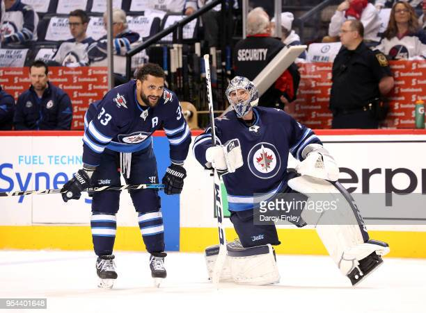Dustin Byfuglien and goaltender Connor Hellebuyck of the Winnipeg Jets look on during the pregame warm up prior to NHL action against the Nashville...