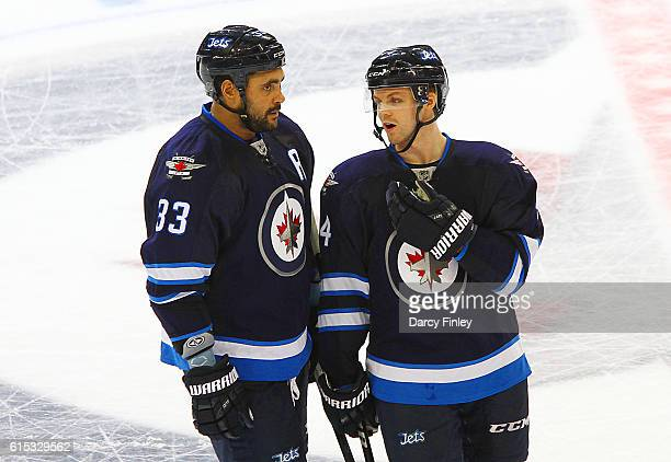 Dustin Byfuglien and Josh Morrissey of the Winnipeg Jets discuss strategy during a second period stoppage in play against the Boston Bruins at the...