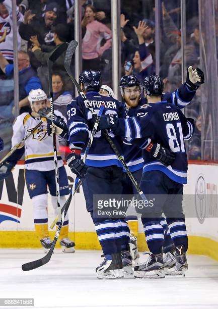 Dustin Byfuglien Kyle Connor and Adam Lowry of the Winnipeg Jets celebrate a third period goal against the Nashville Predators at the MTS Centre on...
