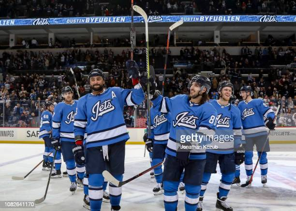 Dustin Byfuglien Mathieu Perreault and Nikolaj Ehlers of the Winnipeg Jets are all smiles as they salute the fans following a 63 victory over the...