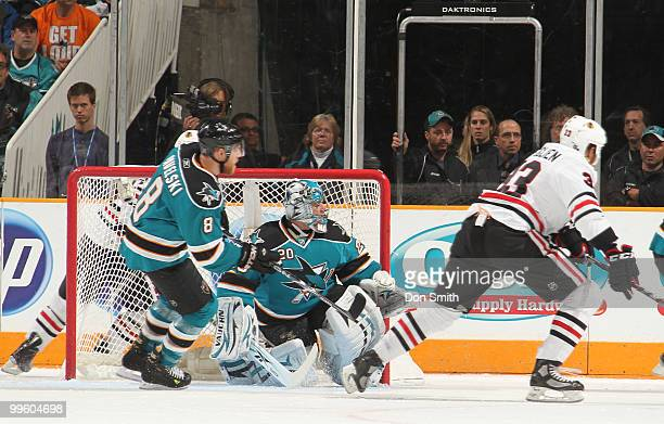 Dustin Byfuglien of the Chicago Blackhawks and Evgeni Nabokov and Joe Pavelski of the San Jose Sharks watch the puck in Game One of the Western...