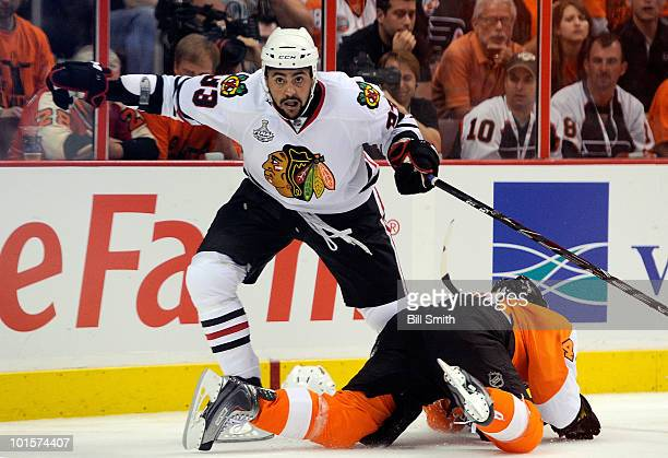 Dustin Byfuglien of the Chicago Blackhawks and Patrick Maroon of the Philadelphia Flyers tangle up behind the net during the third period of Game...