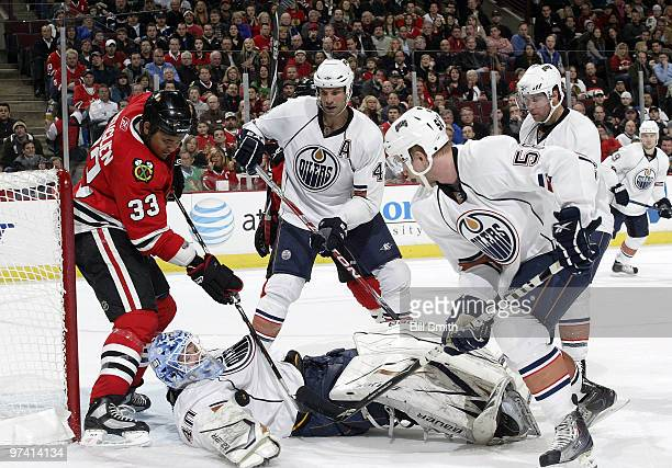 Dustin Byfuglien of the Chicago Blackhawks Jason Strudwick and Johan Motin of the Edmonton Oilers work to get the puck which lands on goalie Devan...