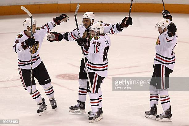 Dustin Byfuglien of the Chicago Blackhawks reacts with teammates Niklas Hjalmarsson Patrick Kane and Jonathan Toews after Byfuglien scores a second...