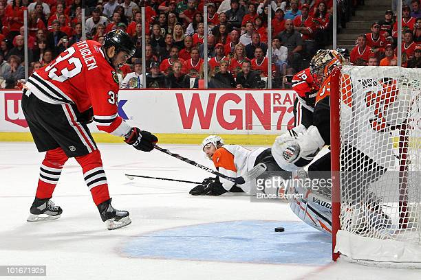Dustin Byfuglien of the Chicago Blackhawks scores a power play goal in the second period against Brian Boucher of the Philadelphia Flyers in Game...
