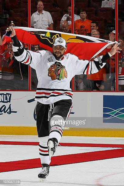 Dustin Byfuglien of the Chicago Blackhawks skates with the Blackhawks flag after teammate Patrick Kane scored the gamewinning goal in overtime to...