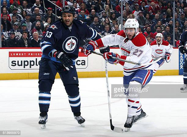 Dustin Byfuglien of the Winnipeg Jets and Alex Galchenyuk of the Montreal Canadiens battle for position as they keep their eye on the play during...