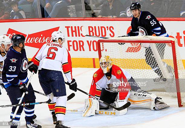 Dustin Byfuglien of the Winnipeg Jets and Alex Petrovic of the Florida Panthers watch as the puck gets behind goaltender Roberto Luongo for a second...