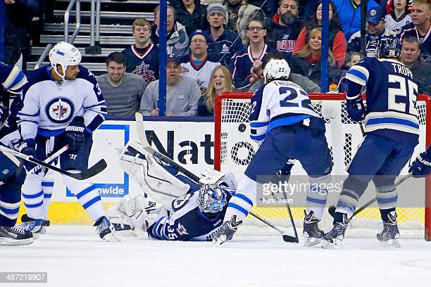 Dustin Byfuglien of the Winnipeg Jets and Chris Thorburn of the Winnipeg Jets watch as Fedor Tyutin of the Columbus Blue Jackets beats Al Montoya of...