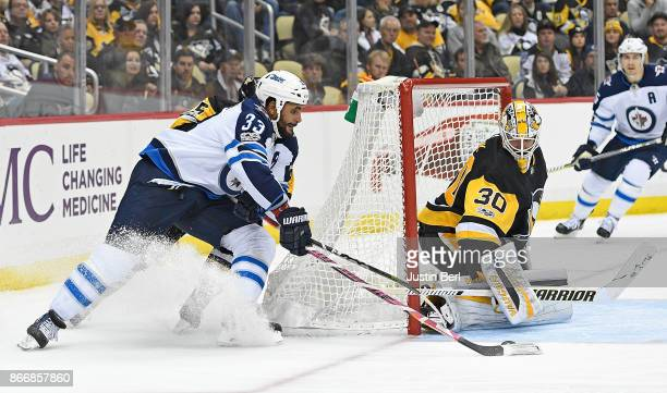 Dustin Byfuglien of the Winnipeg Jets attempts a wrap around shot on Matthew Murray of the Pittsburgh Penguins in the third period during the game at...