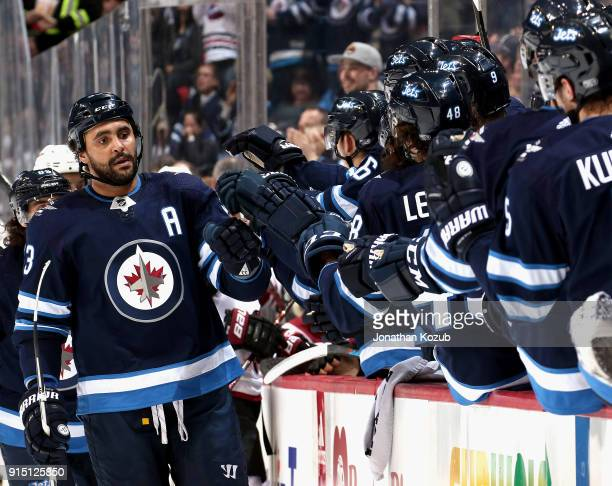 Dustin Byfuglien of the Winnipeg Jets celebrates his first period goal against the Arizona Coyotes with teammates at the bench at the Bell MTS Place...