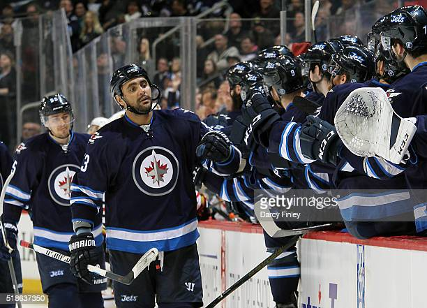 Dustin Byfuglien of the Winnipeg Jets celebrates his third period goal against the Chicago Blackhawks with teammates at the bench at the MTS Centre...