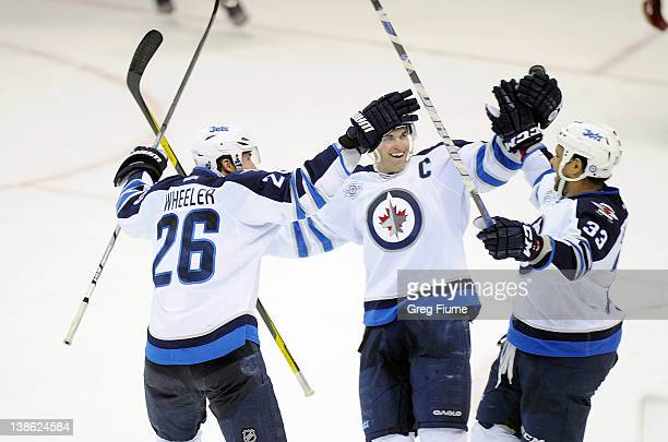 Dustin Byfuglien of the Winnipeg Jets celebrates with Andrew Ladd and Blake Wheeler after scoring in the third period against the Washington Capitals...