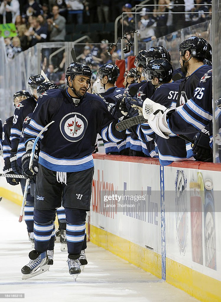 Dustin Byfuglien #33 of the Winnipeg Jets celebrates with teammates at the bench after a third period goal by teammate Blake Wheeler #26 (not shown) against the Dallas Stars at the MTS Centre on October 11, 2013 in Winnipeg, Manitoba, Canada.