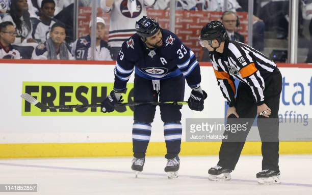 Dustin Byfuglien of the Winnipeg Jets chats to a referee during a break in action with the St Louis Blues in Game One of the Western Conference First...