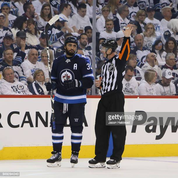 Dustin Byfuglien of the Winnipeg Jets chats with a refere during a break in play against the Minnesota Wild in Game Five of the Western Conference...