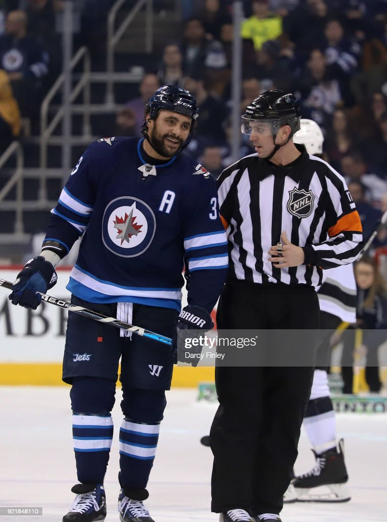 Dustin Byfuglien #33 of the Winnipeg Jets chats with referee Frederick L'Ecuyer #17 during a second period stoppage in play against the Los Angeles Kings at the Bell MTS Place on February 20, 2018 in Winnipeg, Manitoba, Canada.