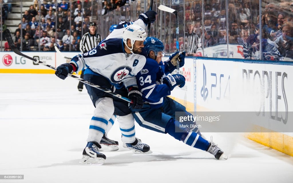 Dustin Byfuglien #33 of the Winnipeg Jets checks Auston Matthews #34 of the Toronto Maple Leafs during the third period at the Air Canada Centre on February 21, 2017 in Toronto, Ontario, Canada.