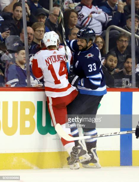 Dustin Byfuglien of the Winnipeg Jets checks Gustav Nyquist of the Detroit Red Wings into the boards during third period action at the Bell MTS Place...