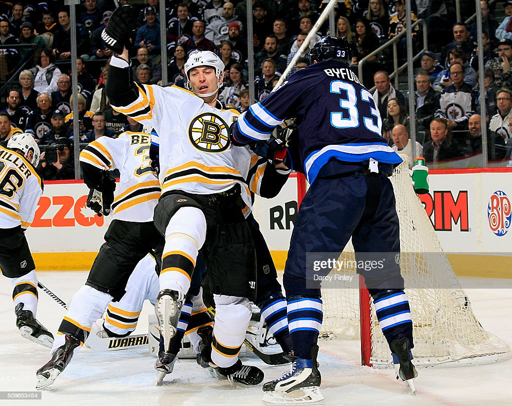 Dustin Byfuglien #33 of the Winnipeg Jets checks Zdeno Chara #33 of the Boston Bruins to the side of the net during first period action at the MTS Centre on February 11, 2016 in Winnipeg, Manitoba, Canada.