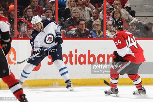 Dustin Byfuglien of the Winnipeg Jets clears the puck against JeanGabriel Pageau of the Ottawa Senators during an NHL game at Canadian Tire Centre on...
